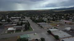 Aerial rural town Main Street high mountain plateau. Business center of city. Rural community southern Utah, San Juan County. High mountain plateau, dry farm landscape. Remote agriculture economy. Homes, fields and small town business. 4K HD video footage. Despain Rekindle Photo. 039
