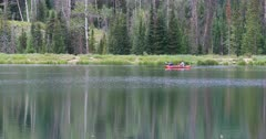 Couple in canoe high forest mountain lake Utah. Scenic high mountain lake used for recreation, canoe and fishing. Campgrounds on shore. Couples and families enjoy the great outdoors and nature. Pine and aspen forest. Calm and relaxing pleasure. 4K HD video footage. Despain Rekindle Photo. 1234