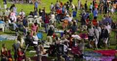 Crowd summer celebration blurred 4K. Fourth of July, American celebration for freedom in small rural town. Parade reflects community values and family morals. Patriotic display of flag, high school bands, royalty floats and fire trucks. Summer Family reunion time. Families gather for fireworks.  DCI 4K HD video footage. Despain Rekindle Photo. 1628