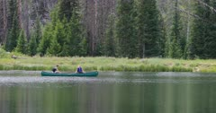 Young couple in love canoe high mountain lake. Scenic high mountain lake used for recreation, canoe and fishing. Campgrounds on shore. Couples and families enjoy the great outdoors and nature. Pine and aspen forest. Calm and relaxing pleasure. 4K HD video footage. Despain Rekindle Photo. 1229