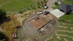 Aerial circle around rural farm home new construction 4K . Construction of rural farm agriculture building. Pouring concrete for footing and foundation. Engineering architectural design. Contractor and workers form base of shed. Modern facility for farming income. Protection if equipment and repairs. 4K video footage. Despain Rekindle Photo. 067