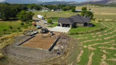 Aerial concrete construction farm house mountain valley. Construction of rural farm agriculture building. Pouring concrete for footing and foundation. Engineering architectural design. Contractor and workers form base of shed. Modern facility for farming income. Protection if equipment and repairs. 4K video footage. Despain Rekindle Photo.