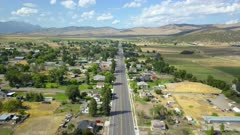 Aerial Main Street rural farming community mountain valley 4K. Spring seasonal weather. Green grass, fields and tree growing in warm temperature. House, home, barns and shed along streets and roads. Small farming community town in mountain valley. Cityscape and agriculture and farming based economy. 4K HD video footage. Despain Rekindle Photo.
