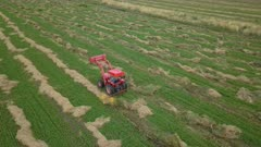 Aerial follow farm tractor fixing hay in field. Aerial rural farming community agricultural economy. Spring summer weather mountain valley green agriculture field. Seasonal rural farm harvest. Alfalfa hay for livestock feeding. Drone flight. 4K HD video footage. Despain Rekindle Photo. 026