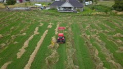 Aerial follow track tractor in farm field working hay. Aerial rural farming community agricultural economy. Spring summer weather mountain valley green agriculture field. Seasonal rural farm harvest. Alfalfa hay for livestock feeding. Drone flight. 4K HD video footage. Despain Rekindle Photo. 026