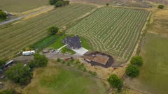 Aerial modern farm house hay field new construction. Aerial rural farming community agricultural economy. New construction. Spring summer weather mountain valley green agriculture field. Seasonal rural farm city. Homes, barns and buildings. Drone flight. 4K HD video footage. Despain Rekindle Photo. 021