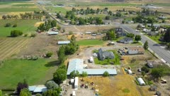 Aerial rural farming community homes sheds fields. Aerial rural farming community agricultural economy. Spring summer weather mountain valley green agriculture field. Seasonal rural farm city. Homes, barns and buildings. Drone flight. 4K HD video footage. Despain Rekindle Photo. 019
