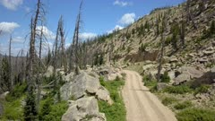 Aerial alpine forest mountain trail road cliff. Skyline Drive off road trail and road central Utah. Alpine peaks, meadows and valley forest. Travel and exploring wilderness outback country landscape and nature. 4K HD video footage. Despain Rekindle Photo. 031