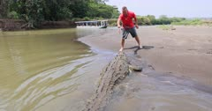Puntarenas Costa dangerous wild crocodile in river man feeding. Dangerous demonstration of wildlife. Central Pacific coast largest city, Puntarenas sits on a long, narrow peninsula. Cruise vacation destination and port. Central America. Beach and surfing. Fishing, coffee and tourism main economic. 4K HD video footage. Despain Rekindle photo. 1840