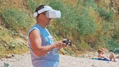 Man using a drone with remote controller wearing virtual reality glasses making photos and videos - Young guy having fun with new technology