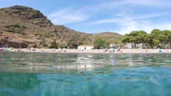 Peaceful beach shore with tourists in summer vacations, Mediterranean sea, Spain, Costa Brava, Catalonia, Cala Joncols, panning shot seen from water surface
