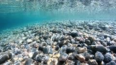 Pebbles underwater below water surface on the seashore, Mediterranean sea, Catalonia, Costa Brava, Spain