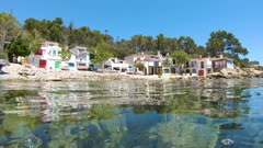 Coastal fishermen houses with boats on the seashore and rocks underwater, Mediterranean sea, Spain, Costa Brava, Cala s'Alguer, Palamos, Catalonia
