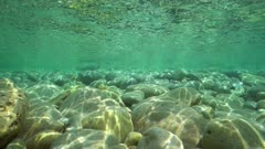 Pebbles in shallow water in the Mediterranean sea with the ripples of water surface, underwater scene, natural sunlight, Javea , Alicante, Valencia, Spain
