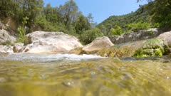 Water flowing in a rocky river, moving camera over and under water surface, Spain, La Muga, Catalonia