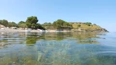 Spain Mediterranean coast peaceful sea shore with small boats seen from water surface and seagrass underwater, Costa Brava, Portlligat, Cadaques, Cap de Creus, Catalonia