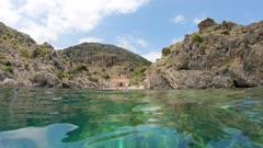 Spain Costa Brava, rocky coastline with a hut in a small cove seen from water surface, Mediterranean sea, Cap de Creus, Cala Gentil, Catalonia