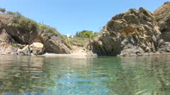 Spain small cove on rocky sea shore seen from water surface and moving camera down underwater, Mediterranean, Costa Brava, Cadaques, Cala Jonquet, Catalonia