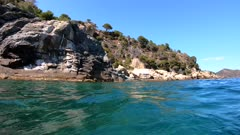 Rocky coast and school of fish underwater (grey mullets), Mediterranean sea, Spain, Costa Brava, Cap de Creus
