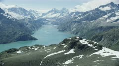 Scenic aerial of snow-capped mountains and a glacier in Glacier Bay National Park and Preserve