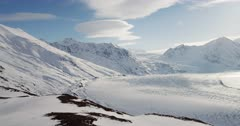 Snow covered mountains near the Knik Glacier, with lenticular clouds