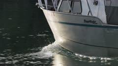 Small boat traveling through the Homer Boat Harbor, Alaska