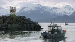 Small boats traveling through the Homer Boat Harbor, Alaska