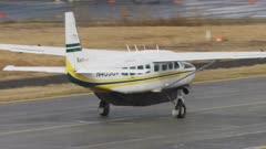 Airplane traveling on a runway near Bethel, Alaska on a rainy day