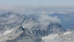 Aerial shot of clouds hanging over the snowy Tordrillo Mountains in Southcentral Alaska