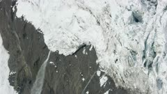 Aerial shot of a waterfall receding from a melting glacier in the snowy Tordrillo Mountains in Southcentral Alaska