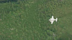 UHD aerial of twin propeller airplane flying over Alaska forest