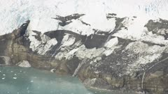 UHD Aerial of melting glacier with flowing waterfall as climate change melts alaska glaciers