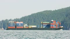UHD shot of cargo shipping barge pulled by tugboat in Alaska