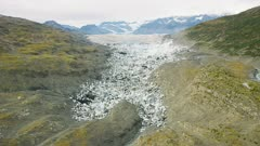 UHD aerial of meltion glacier after glacial dam blowout  leaving icebergs grounded