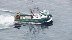 UHD aerial of longline fishing boat traveling in calm waters