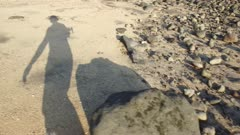 Crew walking on rock-strewn beach.
