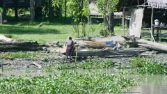 Lady uses River water to produce Sago , hot from the Sun refreshes herself with the river Water