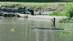 Young Child paddles canoe passed family scene