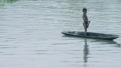A child paddles a traditional canoe in a. Scene that could be hundreds of years old. Unchanged culture.
