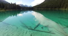 4K Aerial over marsh in to emerald lake, reflections of mountains in water - Not Colour Corrected