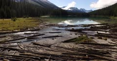4K Aerial up creek over marsh and logs in to emerald lake, reflections of mountains in water - Not Colour Corrected