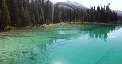 4K Aerial up creek over marsh and logs in to emerald lake, reflections of mountains in water, Reverse direction - Not Colour Corrected
