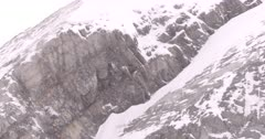4K Raven nest on rocky ledge, wind blowing snow, Zoom in - SLOG2