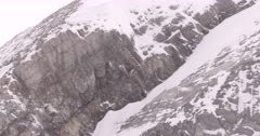 4K Raven nest on rocky ledge, wind blowing snow, Wide Shot - SLOG2