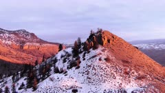 Aerial fly in to sunset coloured rock mountain in the snow