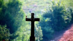 A stone cross at the crossroads of dirt roads with a silhouette of a moving bird