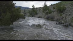 Gardner River right above river looking downriver spring runoff flood stage slow motion wider