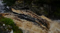 Raging torrent of water at the Falls of Shin in the Scottish Highlands of Sutherland Scotland UK