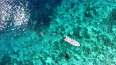 Aerial of dive boat and divers over shallow reef
