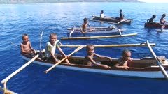 Flyover of Indonesian kids in dugout canoes